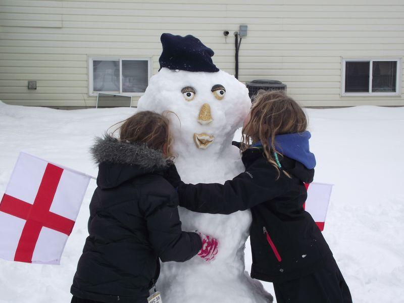 Kids kissing snowman